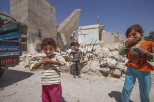 Syriske børn foran bombede huse
